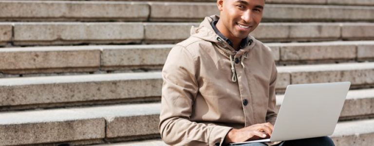 young man of color sitting on steps outside with laptop