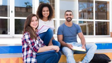 group of college students sitting on steps outside