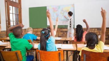 students raising hands in classroom with teacher at the front pointing to a map