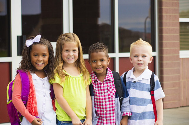 four young children standing together on the first day of school
