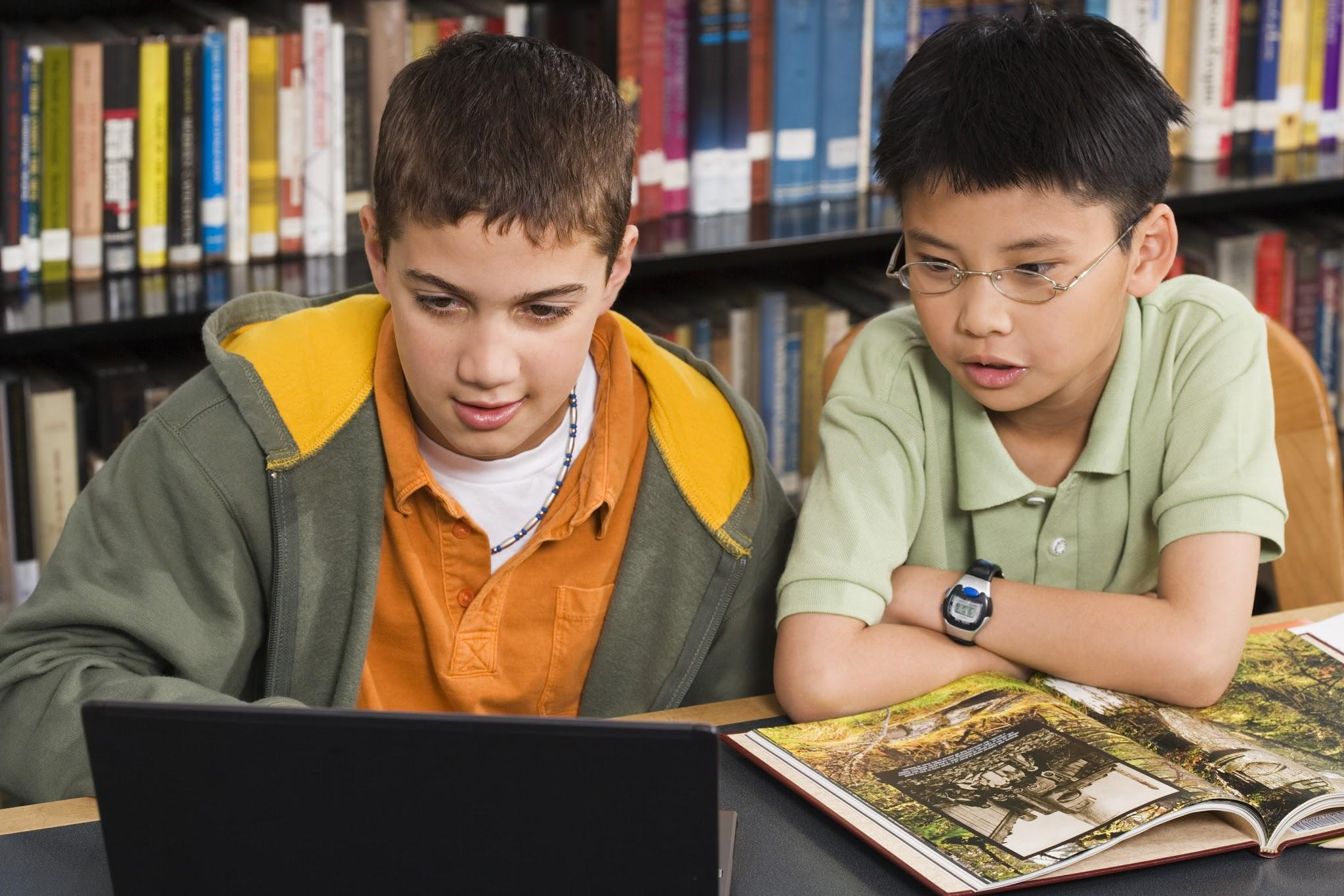 Two elementary school students working on a laptop at a library
