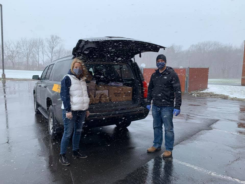 District staff packing school van with lunches for families.