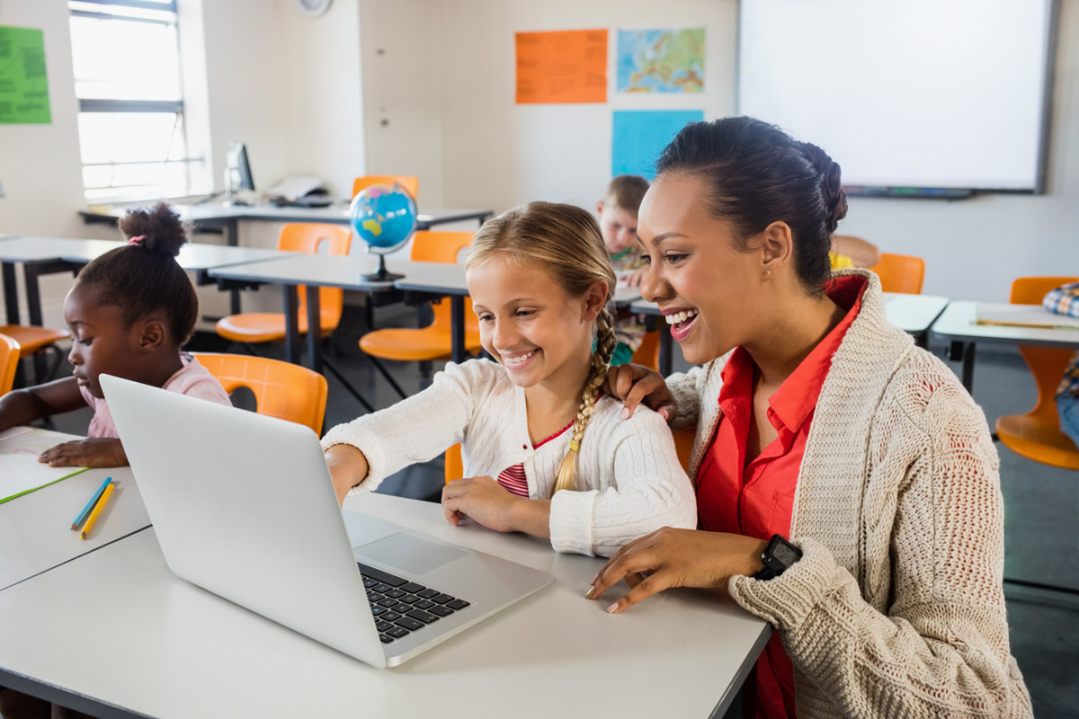 Teacher helping student at desk in classroom