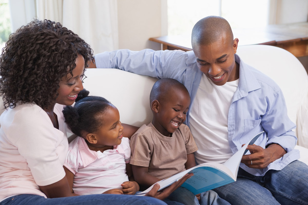 Parents reading book to children