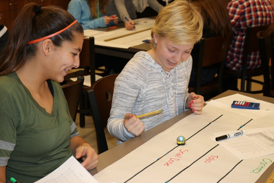 Two students run a time trial on the snail dose track of their ozobot robot.