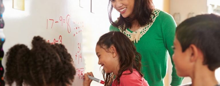 teacher at chalkboard with young students