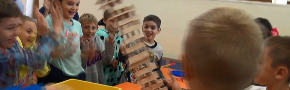 Students excited as a tower of blocks fall over.