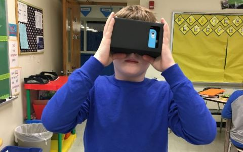 A student using his phone to experience virtual reality.