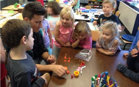 Noah L., a high schooler, completing a STEM bin challenge in one minute with the first grade class.