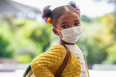 young student wearing mask and backpack