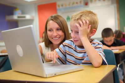 Student and teacher using a laptop