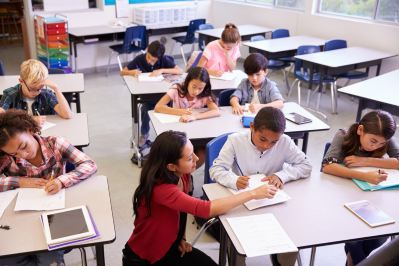 Teacher working at students desk in classroom