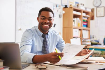 smiling teacher at desk
