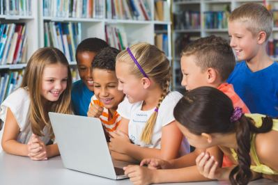 Young students gathered around computer.