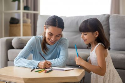mother and preschool daughter writing
