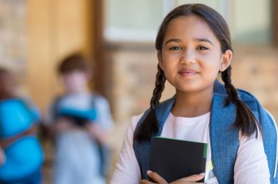 young girl in school wearing backpack