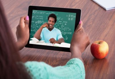 Student holding a tablet showing image of teacher