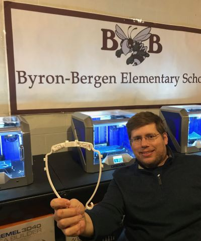 STEAM Lab Teacher Craig Schroth holds up a section of a completed face shield