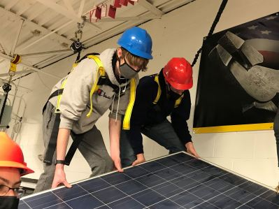 Two students on roof installing a solar panel in a CTE classroom.