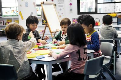 Young students working with shapes and toys at a table