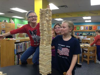 Fourth graders using KEVA Planks to make the tallest and widest structure