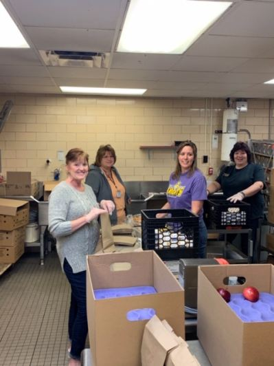 District staff packing lunches in school's kitchen.