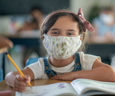 young student in classroom wearing mask