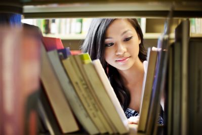 Student looking for books in a library