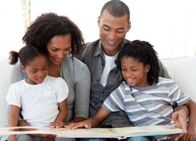 family of four reading a book together