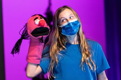 Student performing a puppet show wearing a face mask
