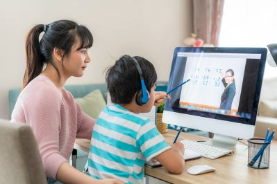 Mother helping child working on math at computer