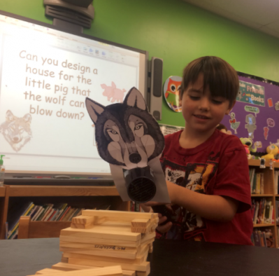 A kindergarten student testing out his KEVA plank house for the Three Little Pigs