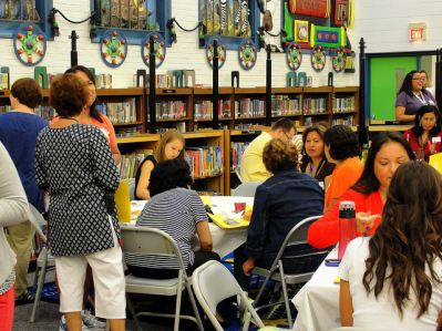 Teachers and staff gathered for an event in a library