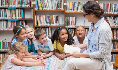 Teacher reading book with students
