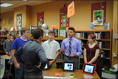 Students presenting to teachers, parents and community members in a library about the Constitution