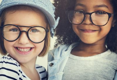 two smiling students wearing glasses