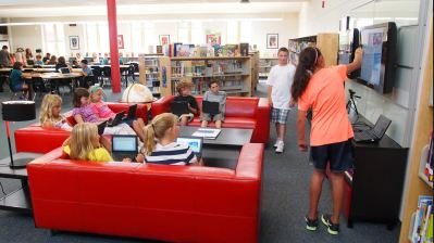 Students working together on a project at a library using modern technology