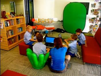 Elementary school students working together with computers at a library