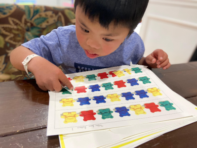 Student pointing to image of teddy bear manipulatives arranged in patterns