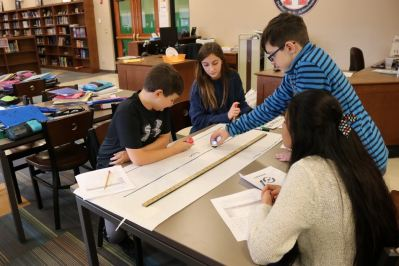 Four students work as a team on their meter-long track.