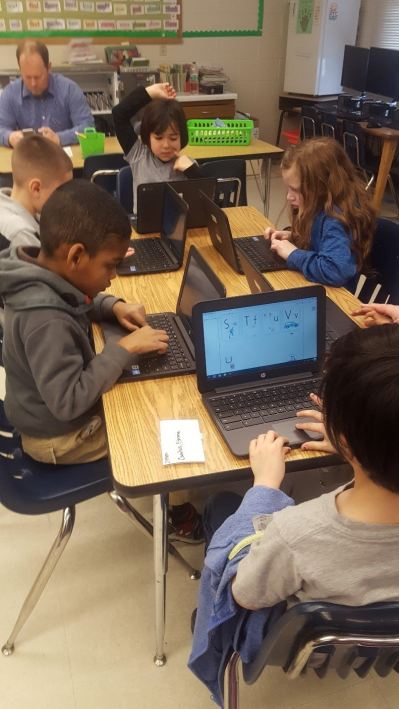 Students learning the alphabet on laptops in class
