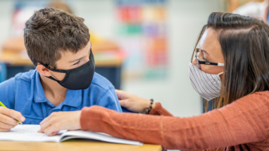 student and teacher in classroom wearing masks