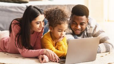 two parents help their child work on a laptop computer
