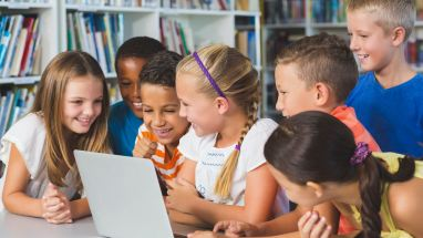group of smiling students at laptop
