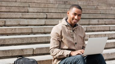 Student sitting outside on steps with laptop